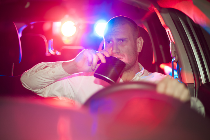 Male driver drinks from flask with police lights flashing behind him